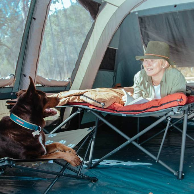 Female camper and dog inside the tent