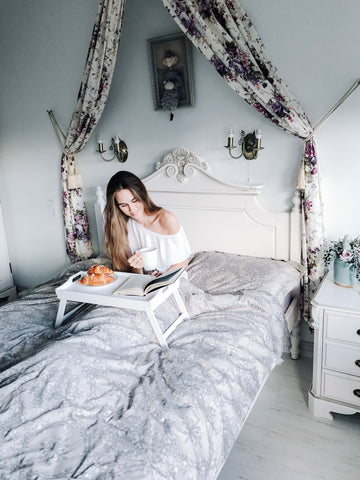 girl drinking coffee and eating breakfast in bed