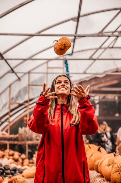 woman throws pumpkin in the air