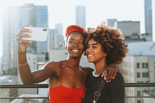 two women taking selfie in city