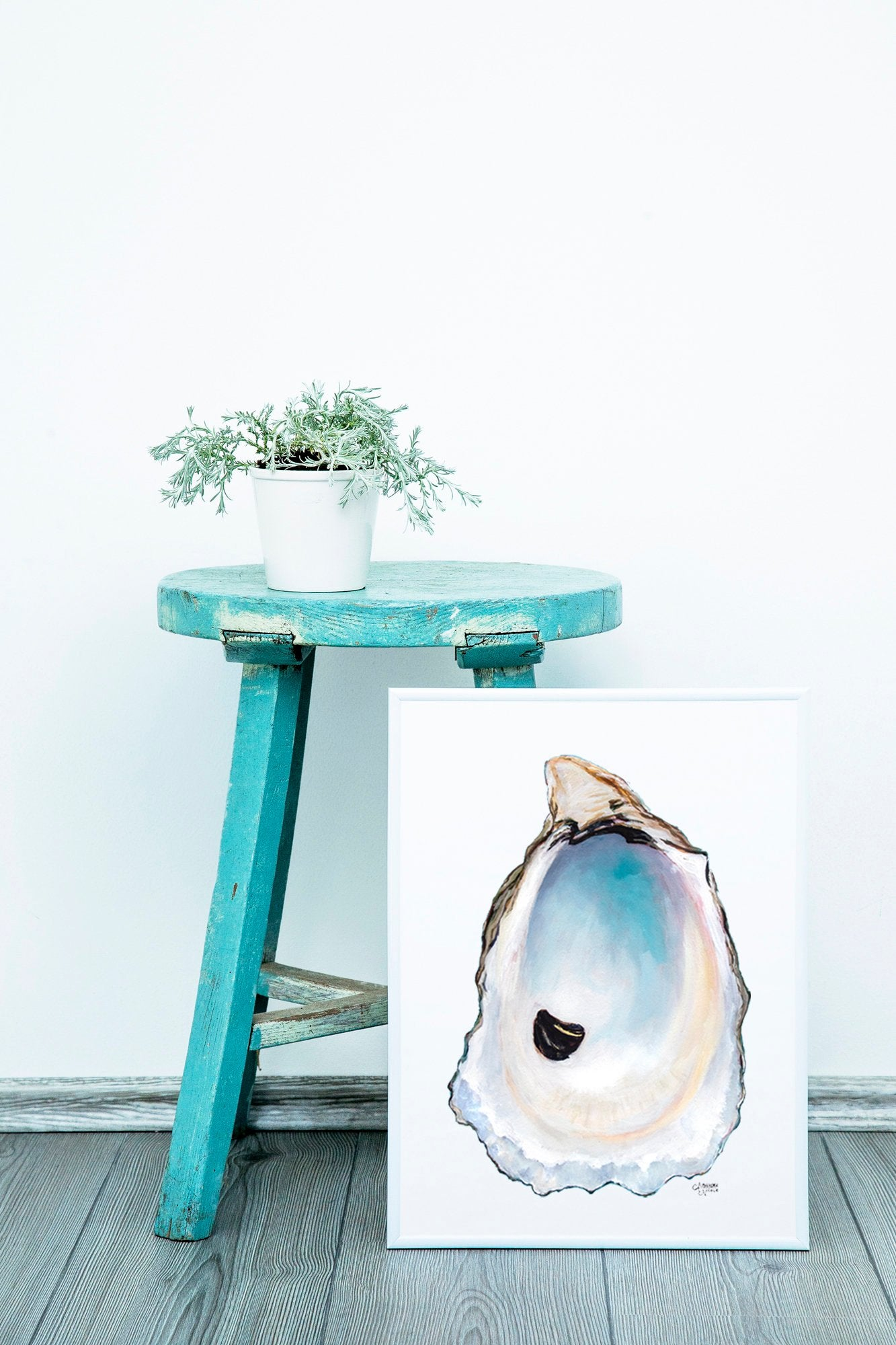 Oyster Shell Art Print resting against a blue stool. Art by Coastal Artist Alexandra Nicole $27