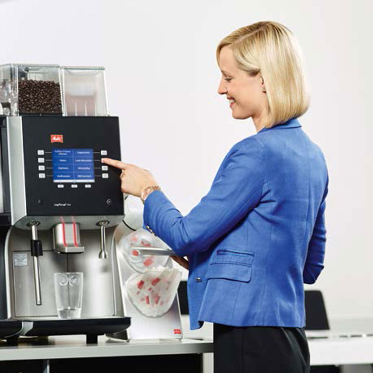 Lady using the buttons on Melitta Cafina XT4 Bean To Cup Coffee Machine
