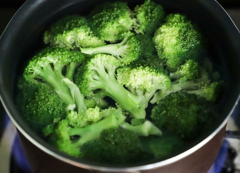 Chopped up broccoli boiling in a pot