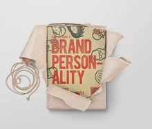Load image into Gallery viewer, The how to hack a brand personality A4 notepad, with 50 sheets of workshop ready activities, being unwrapped from its craft paper packaging in a flatlay style on a muted background.