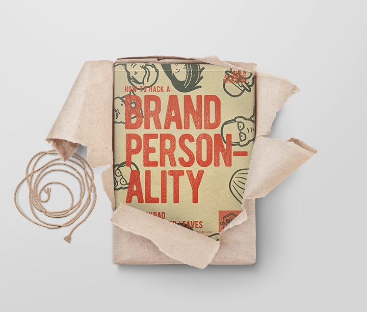 The how to hack a brand personality A4 notepad, with 50 sheets of workshop ready activities, being unwrapped from its craft paper packaging in a flatlay style on a muted background.