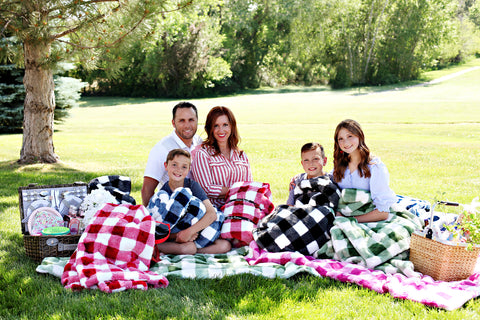 Family having a picnic with Minky Couture Buffalo check blankets in pink, black, navy and green.