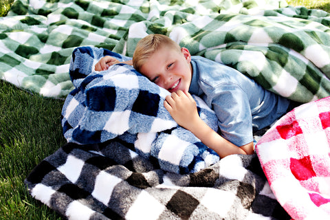 Boy surrounded by buffalo check Minky Couture designer blankets while lying in the grass.