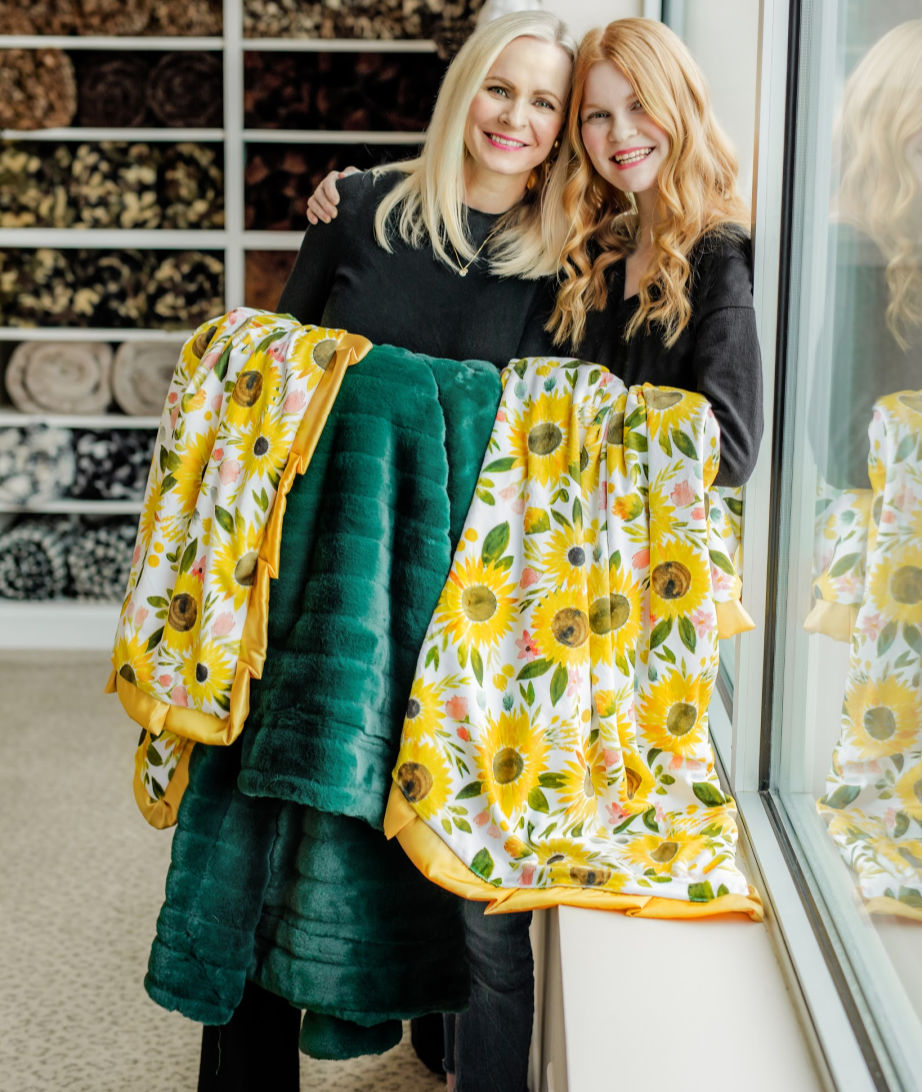 Mother and daughter holding green and sunflower themed blankets by Minky Couture.