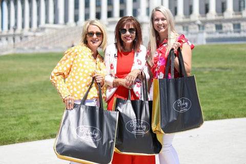 Three women holding reusable Minky Couture shopping bags