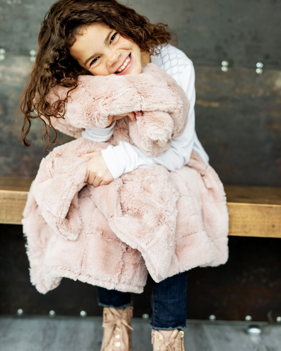 Little girl hugging an urban blush pink blanket by Minky Couture.