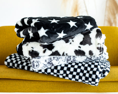 Four black and white patterned Minky Couture plush blankets stacked on a yellow couch.