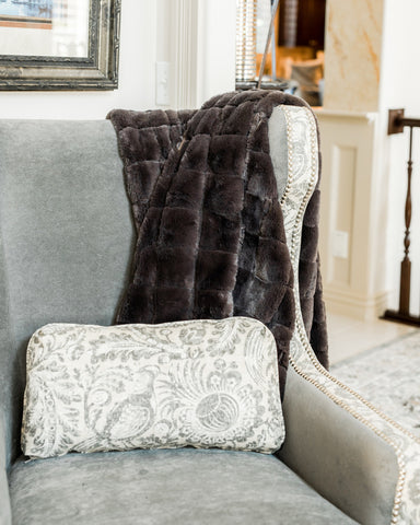 Urban Charcoal Blanket by Minky Couture laid over a gray arm chair.