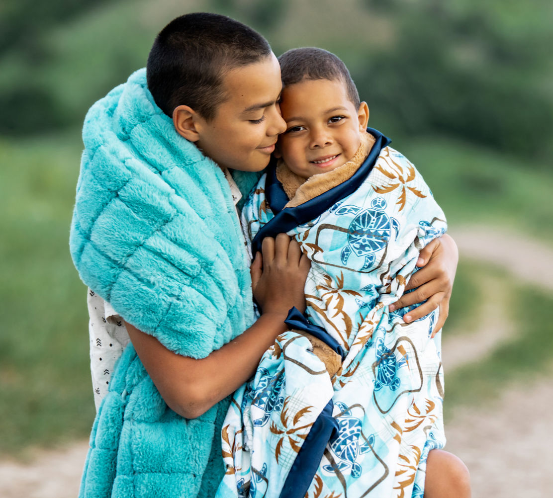 Two brothers snuggled up in the urban tiffany blue and tiki turtle - gold blankets by Minky Couture.