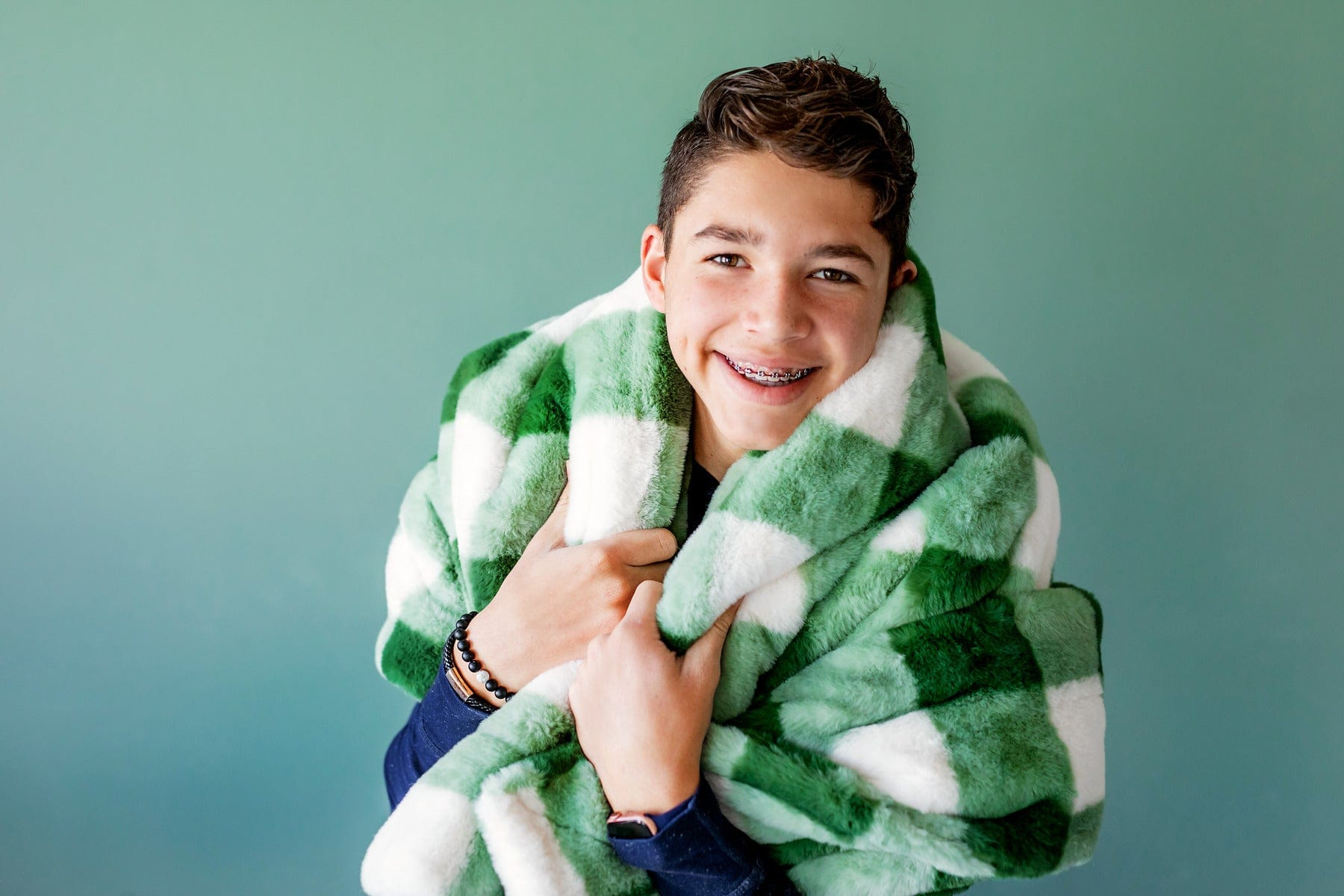 Boy standing in front of a green wall with the Urban Buffalo Check Green blanket by Minky Couture. Zoom - 1
