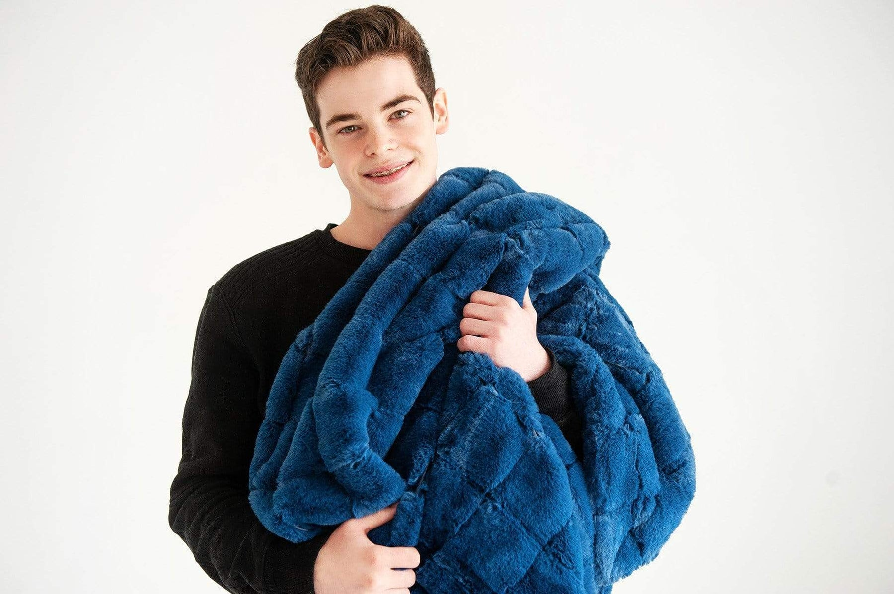 Young man standing holding the Urban Navy blanket by Minky Couture. Zoom - 2
