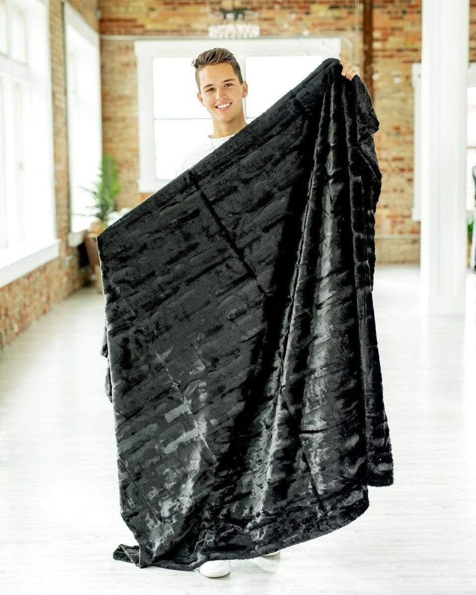 Young man holding a silky black plush blanket by Minky Couture.  Zoom - 2