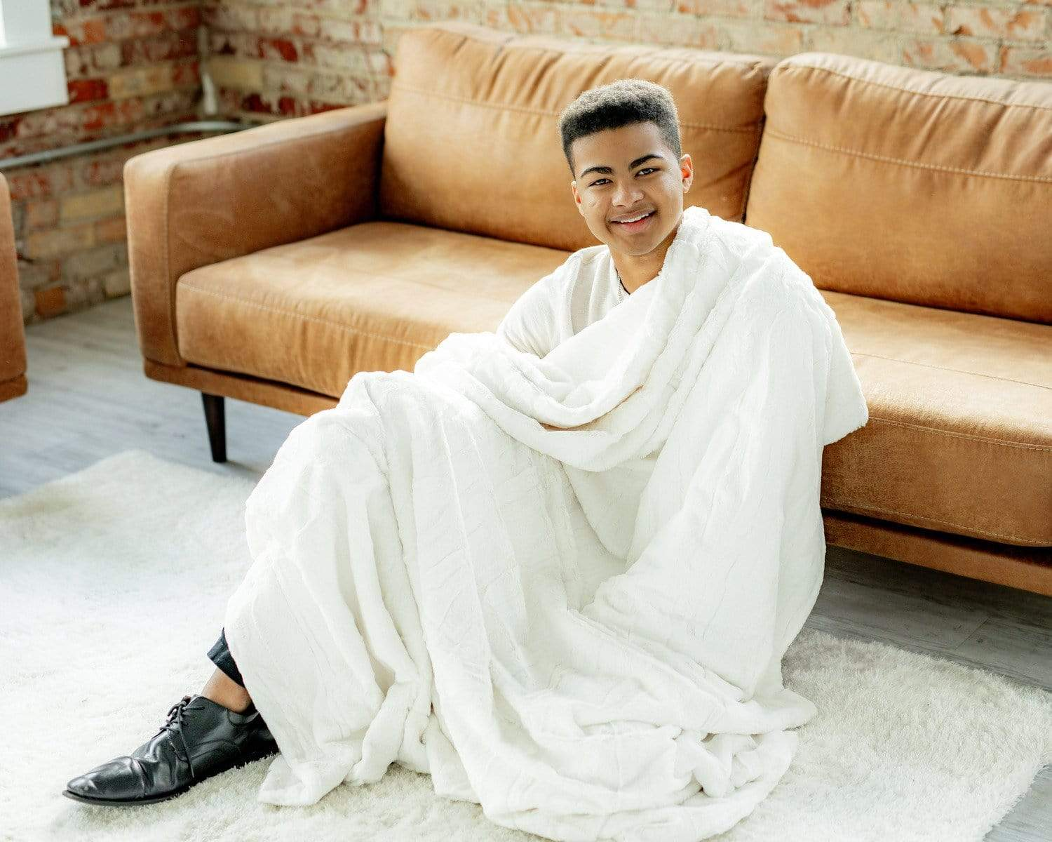 Young man sitting with the sorbet vanilla blanket by Minky Couture.  Zoom - 3