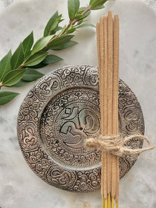 Om incense plate with a bundle of incense.