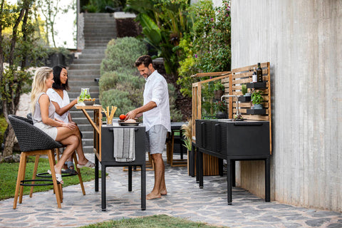Outdoor kitchen with teak elements and a bar section