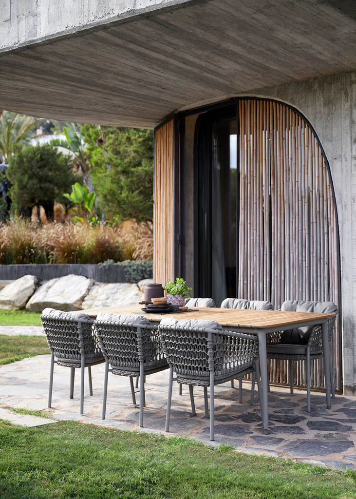 Cosy outdoor space with comfortable outdoor dining chair and teak dining table