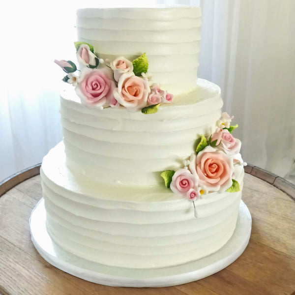 White buttercream 3-tier round cake. Rustic Drag style with 2 posies of pink and blush sugar roses.