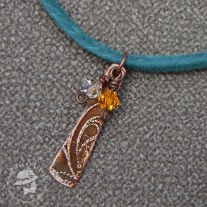 Copper swirl pendant with clear and amber crystals on teal suede