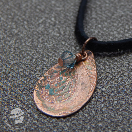 Copper paisley patterned teardrop pendant with smokey blue crystal