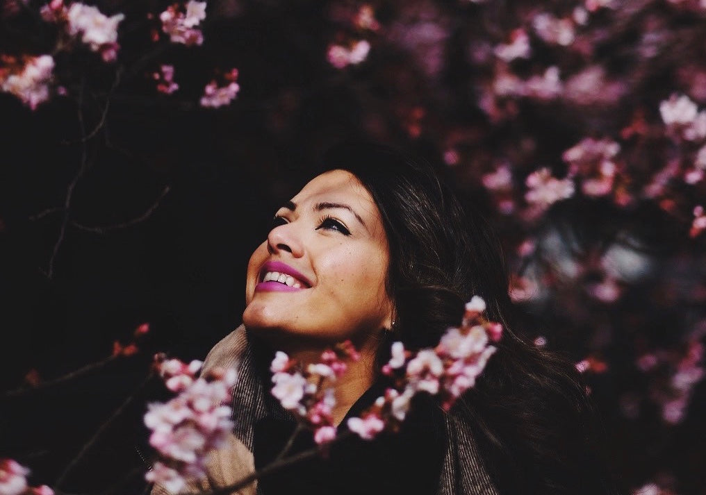 Sara Shah surrounded by flowers gazing up to the sky with a smile