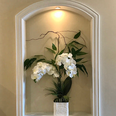 Beautifully modern arrangement with faux white phalaenopsis orchids + lush greenery in a large textured linen ceramic vase