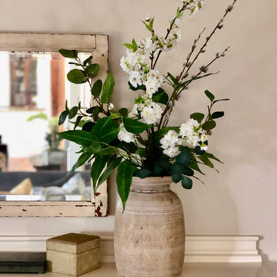 Faux florals + greenery beautifully arranged in a stunning raw wood vase.