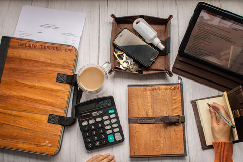 A desk containing notebooks, planners, boards and pouch