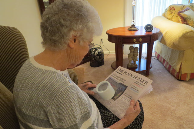 Image of Sheila reading the newspaper with a handheld magnifer