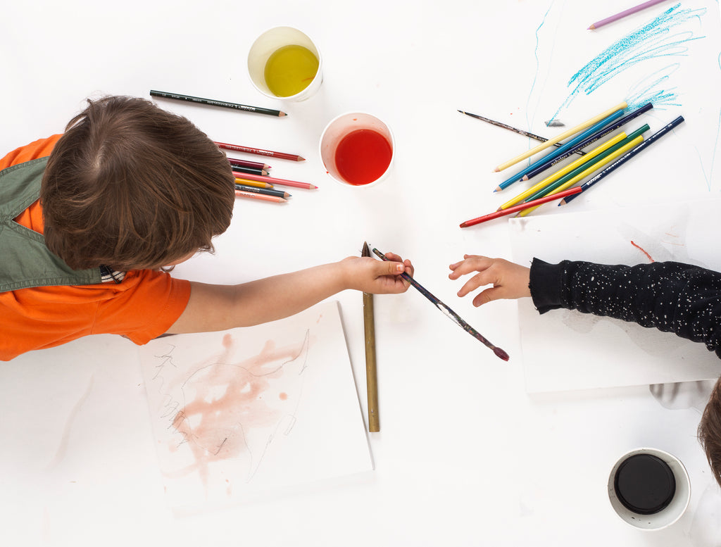 boy and girl toddler drawing with coloured pencils