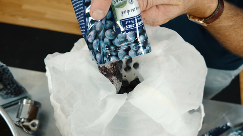 adding freeze dried blueberries to a mesh bag