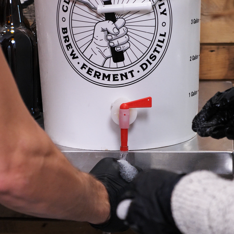 attaching our bottling wand to our bottling bucket