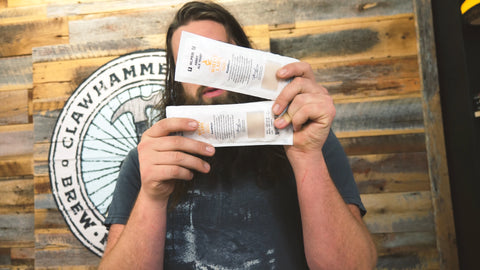 Ross holding two packets of Abbey Ale yeast from White Labs
