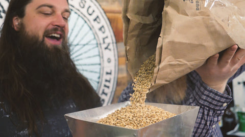 pouring dingemans malt into grain grinder