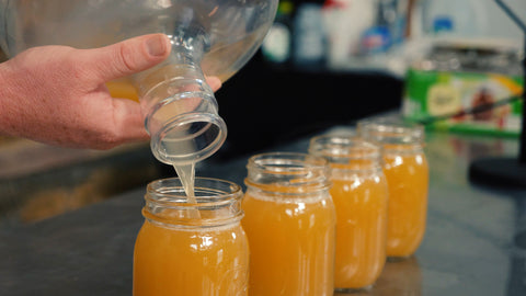 pouring harvested yeast into mason jars for storage