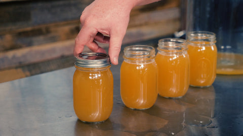 putting a lid on a mason jar filled with harvested yeast
