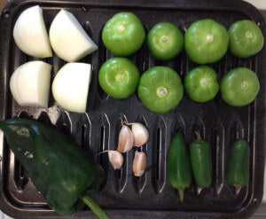 1 big white onion divided into 4 slices, 8 unwrapped tomatillos, 1 poblano chili, 4 cloves of garlic, and 3 jalapeño on a black pan