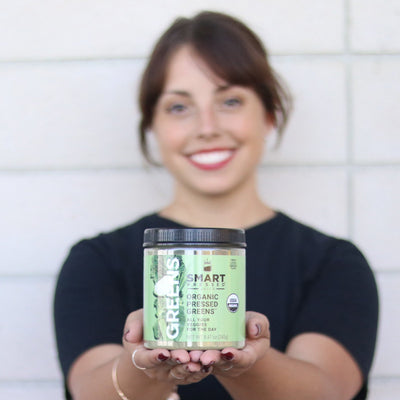 Young girl holding Organic Pressed Greens