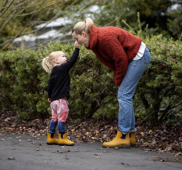 mother and daughter walking, wearing yellow rain boots