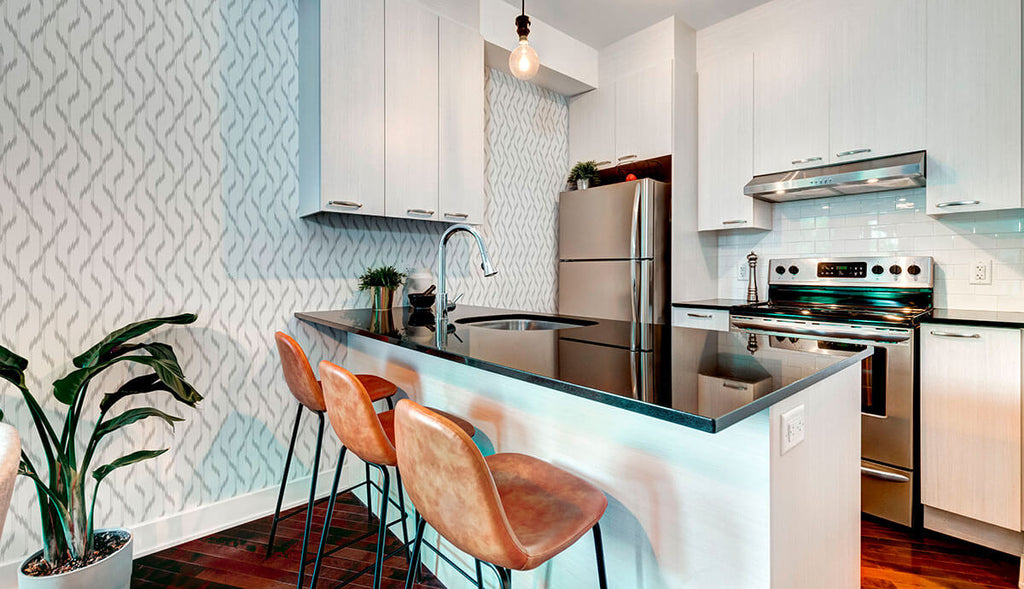 A white kitchen with grey ikat peel and stick wallpaper.