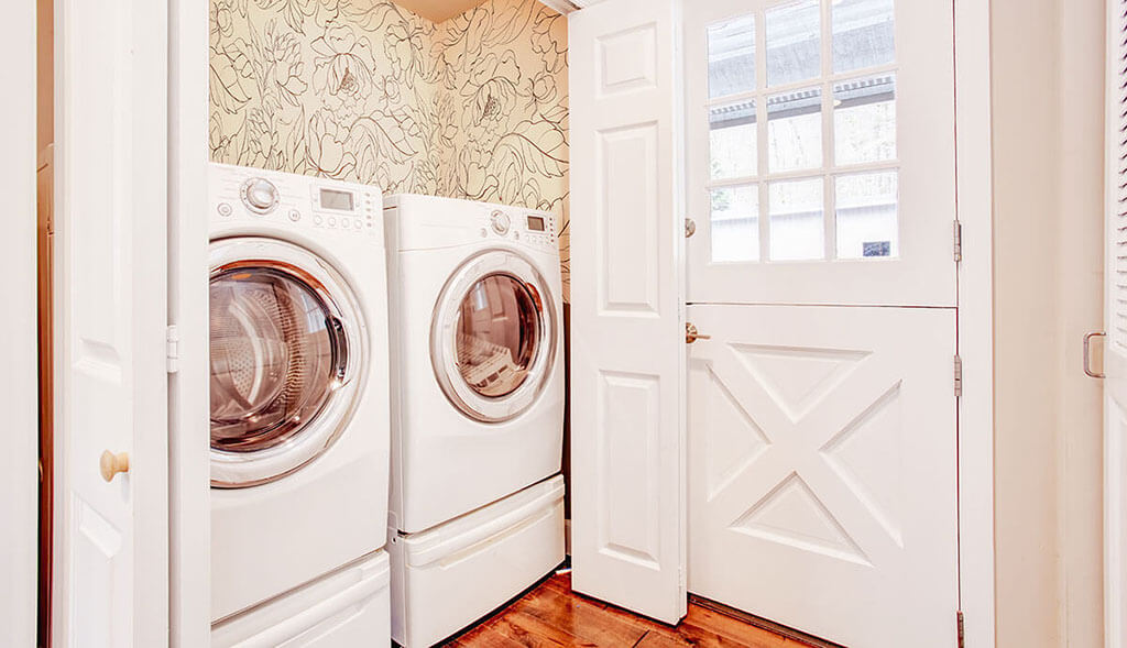 A washer and dryer in a small utility room with beige floral wallpaper and wood flooring.