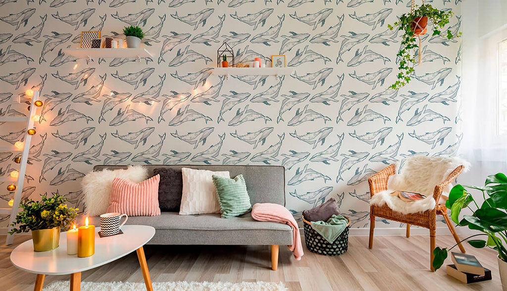 Navy fish wallpaper as an idea for a living room makeover with a couch, string lights, plants, and floating shelves.