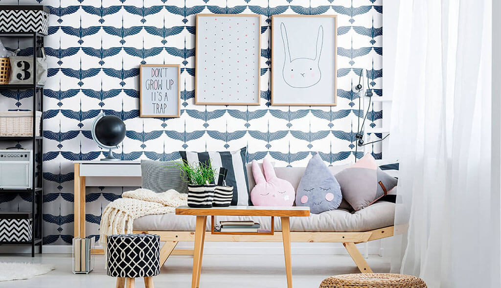 A living room makeover with cute couch pillows, simple wall art, and blue birds wallpaper.