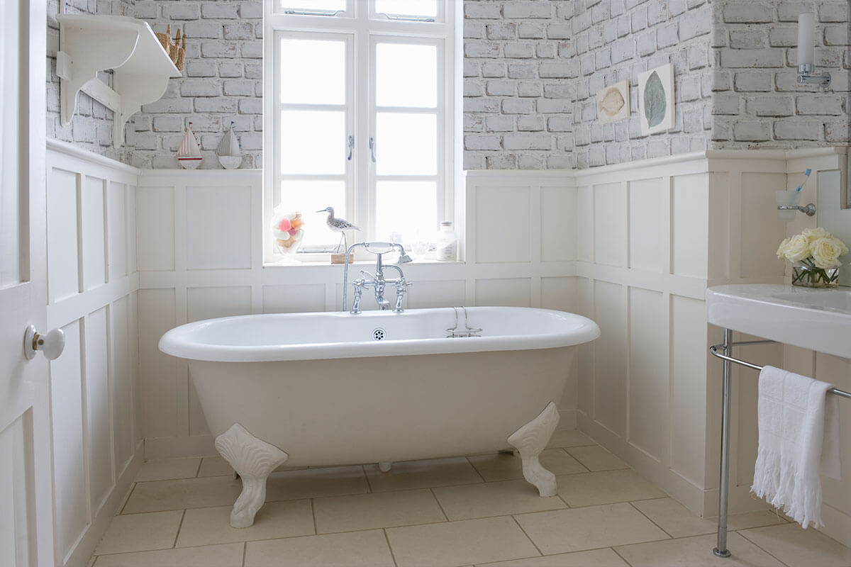 A classic bathtub with brick removable wallpaper in the background