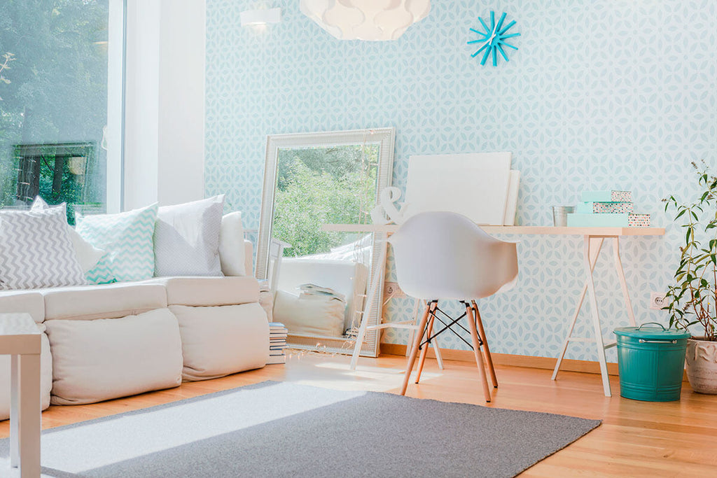 living room with geometric light blue wallpaper and light furniture.