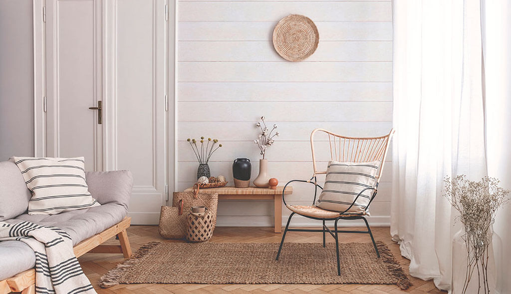 Living room with wicker and wood furniture complimented by white ivory faux shiplap wallpaper.