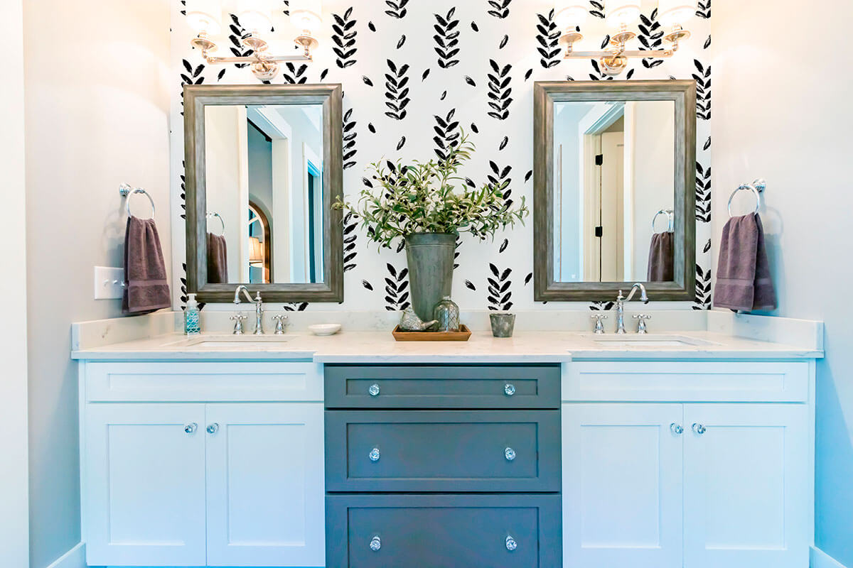 bathroom with gray and white cabinet, two mirrors and a black and white floral wall